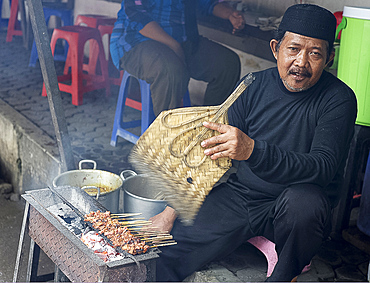Muslim man in the market cooking chicken satay, fanning the charcoal with a palm leaf fan, Solo, Java, Indonesia, Southeast Asia, Asia