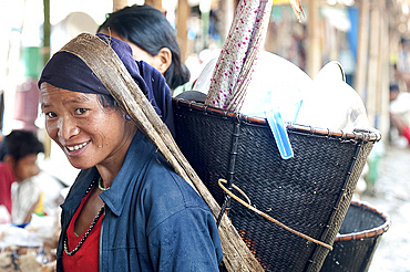 Smiling Naga woman wearing traditional woven cane head basket, shopping in Tizit village weekly local market, Nagaland, India, Asia