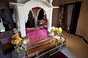 Guru Granth Sahib, the Sikh holy book, covered, in the Darbar Sahib at the Gurudwara Sri Guru Tegh Bahadur Sahib Sikh temple, Dhubri, Assam, India, Asia