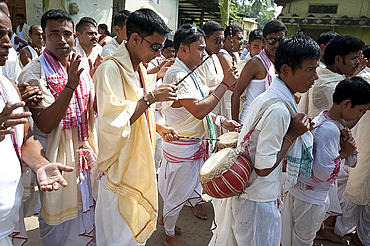 Hindu devotees wearing Assamese white and red gamosa scarves, drumming in Durga puja religious procession, Sualkuchi town, Assam, India, Asia