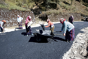 Female roads workers spreading hot tar to resurface roads after monsoon damage high in the hills of Arunachal Pradesh, India, Asia
