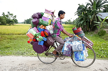 Young village tradesman cycling with a large load of plastic houseware, Majuli, Assam, India, Asia