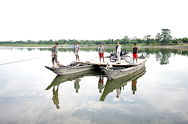 Villagers and a motorbike on a ferry made from two wooden boats and wooden platform, pulled across the Brahmaputra river, Assam, India, Asia