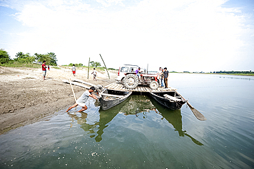Car and tractor on a simple village ferry made from two wooden boats and wooden platform, Brahmaputra river, Majuli, Assam, India, Asia