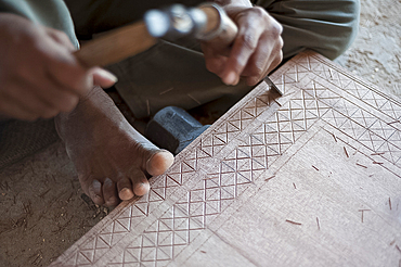 Carpenter chiselling traditional pattern in a piece of wood ready for varnished domestic furniture, Soyla, Kachchh (Kutch), Gujarat, India, Asia