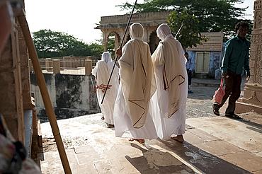 Jain pilgrims in white robes, returning back down Shatrunjaya Hill after walking up to Jain shrines at dawn, Palitana, Gujarat, India, Asia