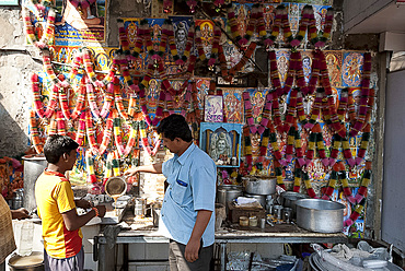 Chai wallah pouring chai (tea) at chai stall decorated with religious posters and malas (garlands), Ahmedabad, Gujarat, India, Asia