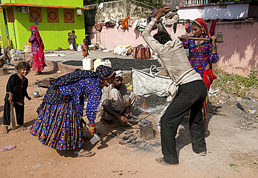 Nomadic tribal women and a man, blacksmiths, beating axe head on hot anvil in the street, Dhenkanal district, Orissa (Odisha), India, Asia
