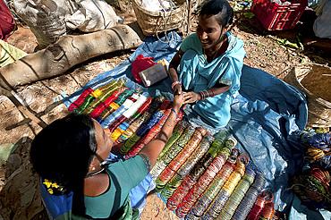 Young woman in turquoise sari selling bangles in Mali weekly tribal market, Guneipada, Koraput district, Orissa (Odisha), India, Asia