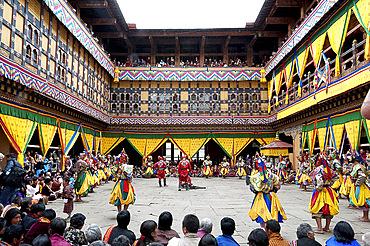 Monks performing religious ceremonial dances in the inner monastery courtyard at the Paro Tsechu (annual monastery festival), Paro, Bhutan, Asia