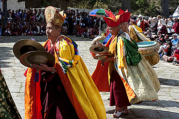 Monk musicians in ceremonial costume playing Bhutanese cymbals and drums at Paro Tsechu (annual monastery festival), Paro, Bhutan, Asia