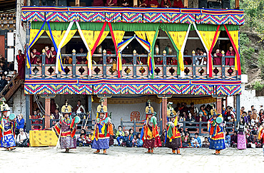 Monks watching dance performance at Paro Dzong (monastery) at the Paro Tsechu (annual monastery festival), Paro, Bhutan, Asia