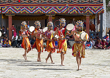 Masked dancers at Paro Dzong (monastery) performing ceremonial masked dance with drums, Tsechu (annual monastery festival), Paro, Bhutan, Asia