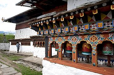 Buddhist man spinning temple prayer wheels outside Dumtse Lakhang Buddhist temple as he perambulates the temple before entering, Bhutan, Asia