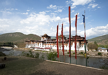 Prayer flags by Punakha dzong (monastery), at the confluence of the Pho chu (Father) and Mo Chu (Mother) rivers, Punakha, Bhutan, Asia