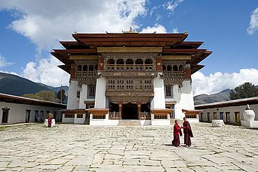 Buddhist monks in stone courtyard of Gangtey dzong (monastery), the largest Nyingmapa monastery in Bhutan, Asia