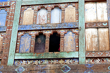 Monk looking out of window with fading blue paint in Wangdue Chhoeling Palace, in need of restoration, Bumthang, Bhutan, Asia