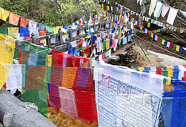 Prayer flags at Mebar Tsho, The Burning Lake, where Pema Lingpa is said to have held a burning butter lamp under the water, Bumthang, Bhutan, Asia