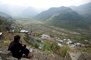 Naga man looks out from Khonoma hilltop village across Naga hills and valley ricefields, Khonoma, Nagaland, India, Asia