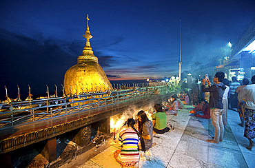 Buddhist pilgrims lighting candles, and visitors at the Golden Rock and Kyaiktiyo Pagoda, Mount Kyaiktiyo, Mon State, Myanmar (Burma), Asia