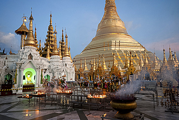 Lit candles placed by devotees at sunset at the Shwesagon Pagoda, a 2500 year old Buddhist pilgrimage site, Yangon, Myanmar (Burma), Asia