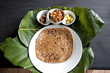 Burmese lunch of chapati with beef curry, vegetables and potatoes, served on teak leaf mat, Kalaw, southern Shan state, Myanmar (Burma), Asia