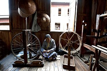 Woman spinning silk thread on a spinning wheel with bicycle wheel, Ko Than hlaing Weaving,  Inpawkhan, Inle Lake, Shan state, Myanmar (Burma), Asia