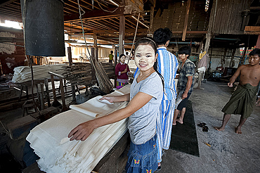 Smiling woman with thanaka paste on her face, folding sheets of pressed, cooked rice in rice noodle factory, Hsipaw, Shan state, Myanmar (Burma), Asia