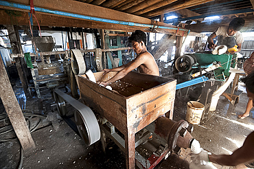 Men squeezing cooked rice through a machine before pressing into flat sheets to make fresh rice noodles, Hsipaw, Shan state, Myanmar (Burma), Asia
