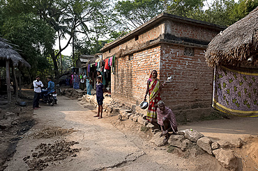 Villagers in typical rural village afternoon scene in the street outside a modern laterite brick built village house, Odisha, India, Asia