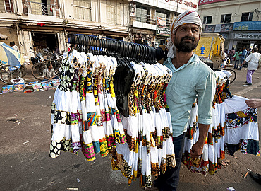 Man in head scarf selling girls' dresses from a rack he carries on his shoulder in the main street in Puri, Odisha, India, Asia