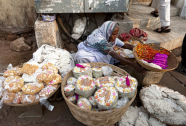 Woman in white sari, selling puja offerings from baskets in the street near the Hindu Jagannath temple dedicated to Lord Vishnu, Puri, Odisha, India, Asia