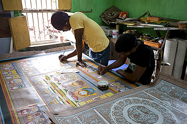 Pattachitra artists painting large traditional Odishan scroll Thia Badhia painting on cloth of the temple of Hindu god Jagannath, Odisha, India, Asia