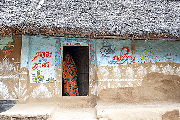 Woman at the door of traditional mud walled Odisha village house decorated with traditional Odishan patterns, Dandasahi, Odisha, India, Asia