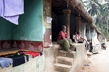 Men sitting chatting in the afternoon on the verandas of their traditional thatch and brick built village homes, rural Odisha, India, Asia