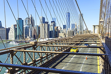 Yellow taxi cab crossing Brooklyn Bridge with the Lower Manhattan skyline behind, New York City, New York, United States of America, North America