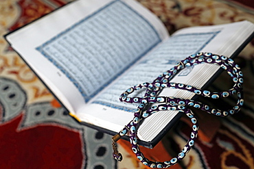 Holy Quran in Arabic and Muslim prayer beads on wood stand, Vietnam, Indochina, Southeast Asia, Asia