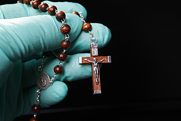 Coronavirus (COVID-19) epidemic, Christian praying rosary beads with protecting glove, France, Europe