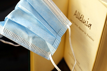 Religion and coronavirus (COVID-19), Bible and disposable surgical mask, Haute-Savoie, France, Europe