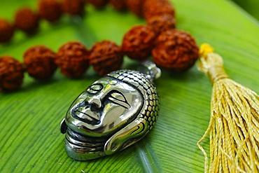 Silver Buddha medallion and prayer beads (mala) on a green leaf, Kep, Cambodia, Indochina, Southeast Asia, Asia