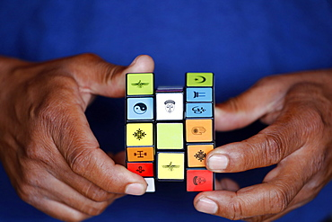 African man with a Rubik's cube with religious symbols, Interreligious and interfaith dialog concept, Madagascar, Africa