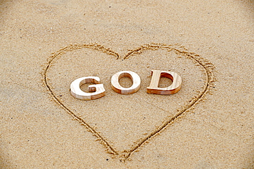 Wooden letters forming the word GOD with heart on a background of beach sand, Christian symbol, Vietnam, Indochina, Southeast Asia, Asia