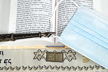 A silver Yad Jewish ritual pointer on a Torah and surgical mask, France, Europe