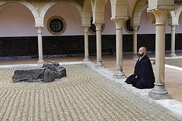 Zen Buddhist monk practising Zazen (meditation) in Orval Trappist Abbey's Zen garden, Belgium, Europe