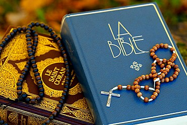 Holy Quran in French with Muslim prayer beads and Bible with rosary, Interfaith symbols between Christianity and Islam, France, Europe