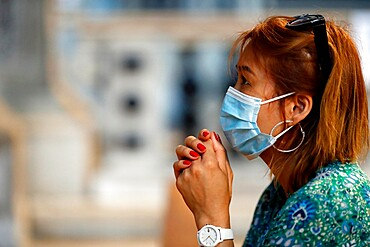 Woman with surgical mask praying in church during coronavirus epidemic (Covid-19), Venice, Veneto, Italy, Europe