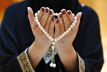 Close up of a Muslim woman's hands in abaya while holding rosary and praying, United Arab Emirates, Middle East