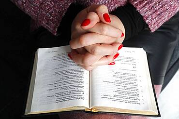 Woman reading the Bible at home, France, Europe