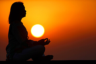 Woman practising yoga pose and meditation at sunset as concept for silence and relaxation, United Arab Emirates, Middle East