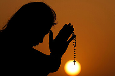 Silhouette of faithful woman praying with rosary beads at sunset as concept for religion, faith, prayer and spirituality, Dubai, United Arab Emirates, Middle East